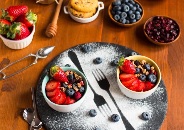 Granen, ontbijt met muesli en vers fruit in kommen op een rustieke houten tafel