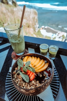 Granola fruityoghurt voor gezond ontbijt met uitzicht op zee