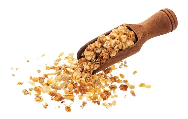 Granola met noten in lepel op witte achtergrond wordt geïsoleerd die