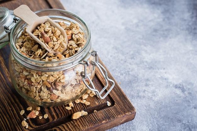 Granola met notenmix in pot op houten bord op stenen tafel achtergrond