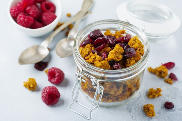Granola met pompoen en gedroogd fruit voor een gezond ontbijt in een glazen pot op een lichte stenen of betonnen tafel. selectieve aandacht.
