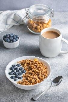 Granola met yoghurt en koffie op een grijze tafel