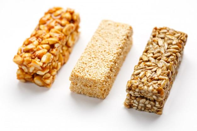 Granola reep met pinda's, sesam en zaden op een rij. bovenaanzicht drie verschillende staven, isoleren