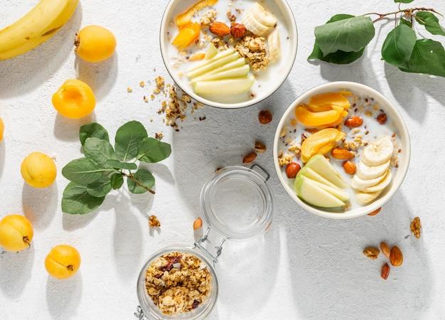 Granolagranen met fruit, noten, melk en pindakaas in kom. gezond ontbijt granen bovenaanzicht
