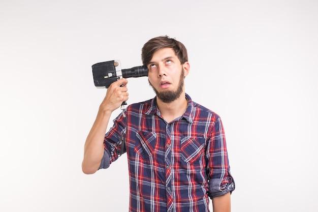 Grap, foto en gebaar concept - grappige dwaze jongeman poseren met camera in de buurt van zijn hoofd op witte achtergrond