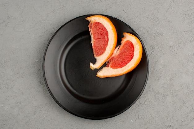 Grapefruit een bovenaanzicht van oranje verse, sappige plakjes in een zwarte plaat en op het lichte bureau
