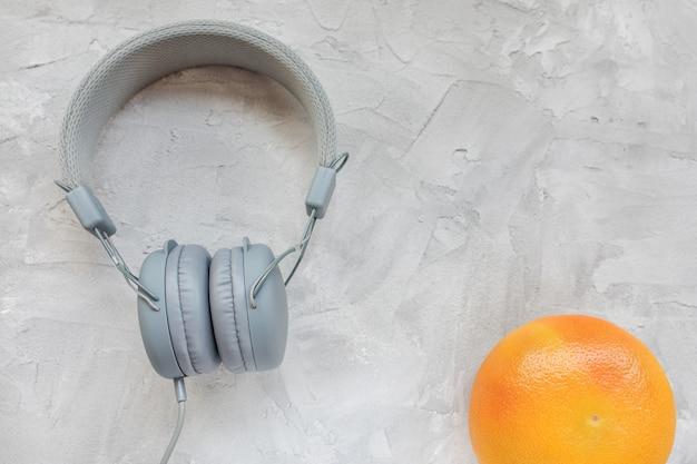 Grapefruit en koptelefoon op grijs