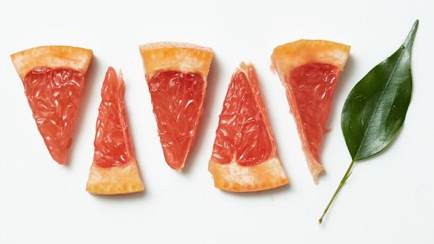Grapefruit met plakdetail en groene bladeren op witte lijst