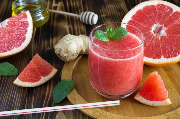 Grapefruit-smoothies, gember en honing op de houten snijplank
