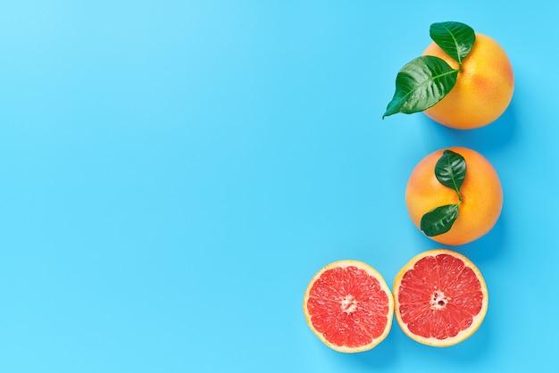 Grapefruit twee met groen blad en de rijpe helft van roze grapefruit op een blauwe achtergrond