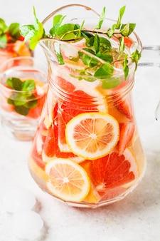 Grapefruitlimonade met citroen en munt in glaskruik.