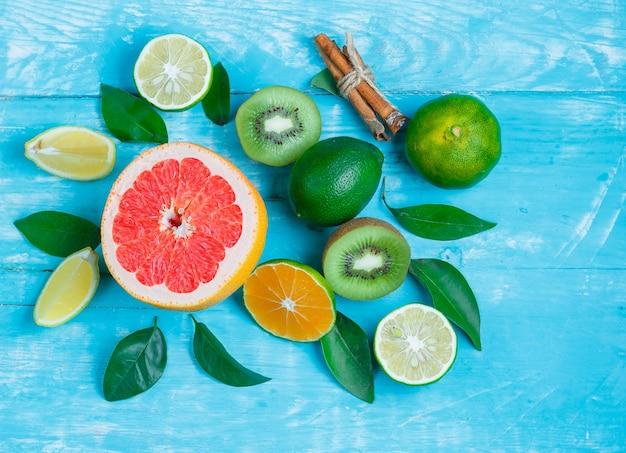 Grapefruitplakken, kiwi, limoenen, bladeren en kaneelstokjes