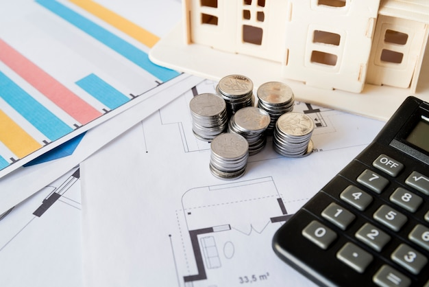 Graph; stapel munten; rekenmachine en huismodel op blauwdruk