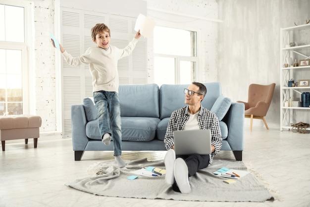 Grapje. aantrekkelijke vrolijke blonde jongen die lacht en springt terwijl hij wat papieren vasthoudt en zijn vader op de vloer zit
