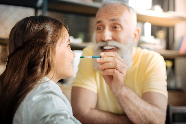 Grapje. speelse gelukkige senior man met een penseel met een waterverf erop en nadert het naar de neus van zijn dochtertje, wil er een stip op zetten