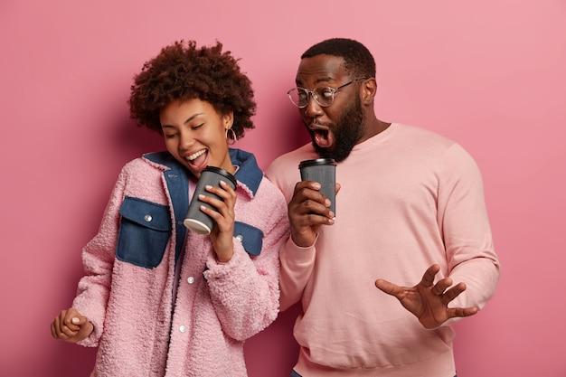 Grappig afrikaans amerikaans stel heeft plezier, houdt papieren kopjes koffie vast, dansen vreugdevol, lachen en voelen zich optimistisch, gekleed in vrijetijdskleding, geïsoleerd op roze ruimte