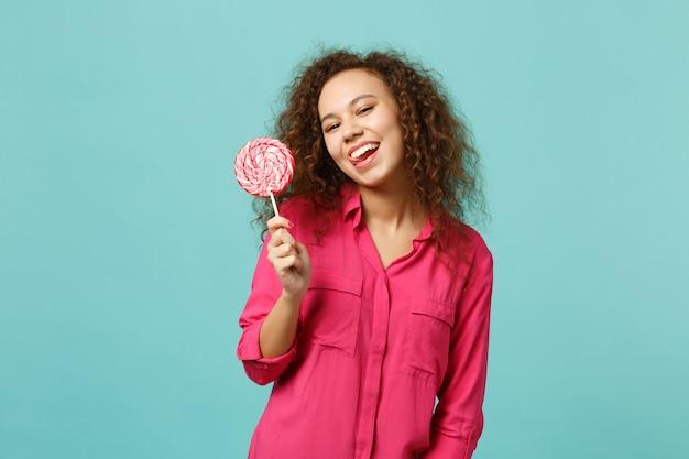 Grappig afrikaans meisje in casual kleding met in de hand roze ronde lolly met tong geïsoleerd op blauwe turkooizen achtergrond in studio. mensen oprechte emoties, lifestyle concept. bespotten kopie ruimte.