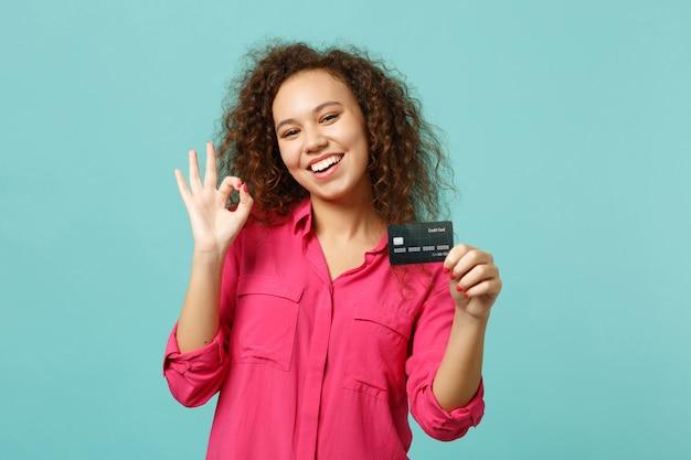 Grappig afrikaans meisje in roze vrijetijdskleding met ok gebaar hold creditcard geïsoleerd op blauwe turquoise muur achtergrond in studio. mensen oprechte emoties, lifestyle concept. bespotten kopie ruimte.