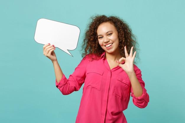 Grappig afrikaans meisje in vrijetijdskleding houdt lege blanco say cloud, tekstballon, met ok gebaar geïsoleerd op blauwe turkooizen achtergrond. mensen oprechte emoties levensstijl concept. bespotten kopie ruimte.