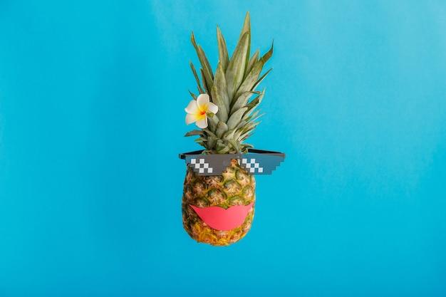 Grappig ananas vrouwelijk gezicht met de bloem van de de zonnebrilplumeria van glimlach rode lippen. tropische zomervruchten zwevende creatieve zomerananas op een blauwe zomerachtergrond in kleur hoge kwaliteit stockfoto