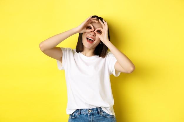 Grappig aziatisch meisje dat door handverrekijkers kijkt en glimlacht, stading over gele achtergrond.