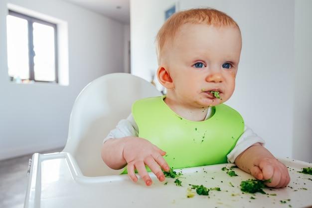 Grappig babymeisje die zachte gekookte groenten zelf eten