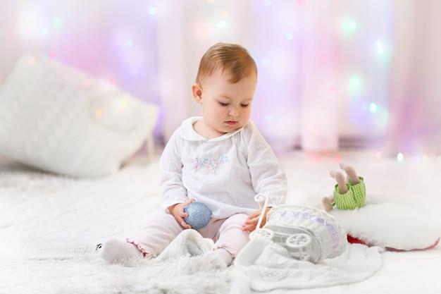 Grappig babymeisje in de woonkamer van kerstmis