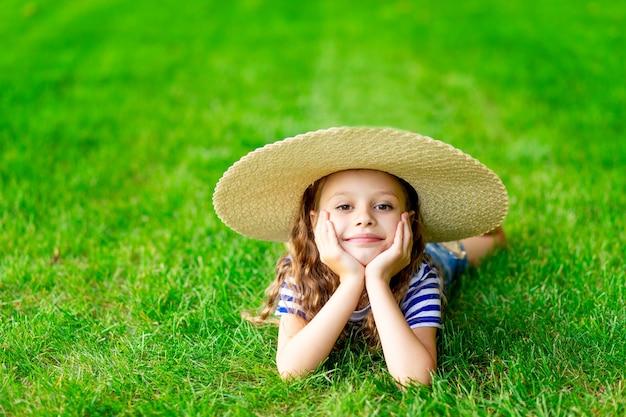 Grappig babymeisje in de zomer op het gazon met een grote strohoed op het groene gras met plezier en vreugde, ruimte voor tekst Premium Foto