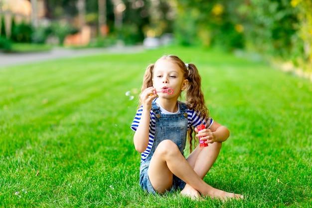 Grappig babymeisje in de zomer op het gazon met zeepbellen op het groene gras, plezier en vreugde, ruimte voor tekst
