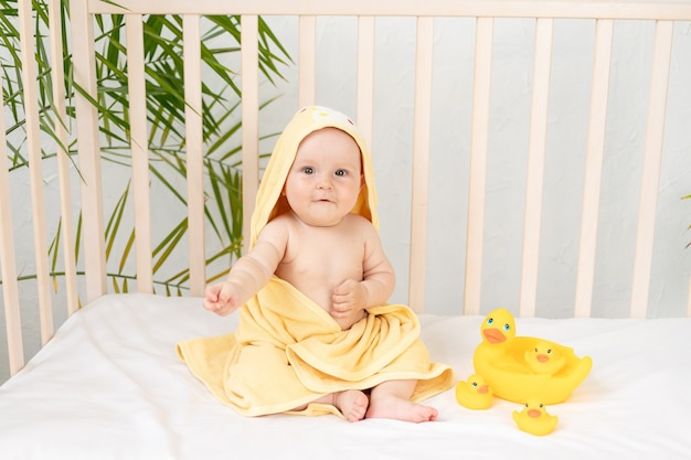 Grappig babymeisje in een gele handdoek na het baden in de badkamer met rubberen eenden in een wieg op een wit katoenen bed, hygiëneconcept