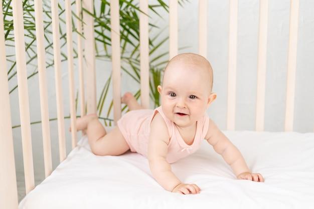 Grappig babymeisje in een wieg in een roze bodysuit voor zes maanden op een wit katoenen bed ligt op haar buik en glimlacht, werd 's ochtends wakker of gaat naar bed