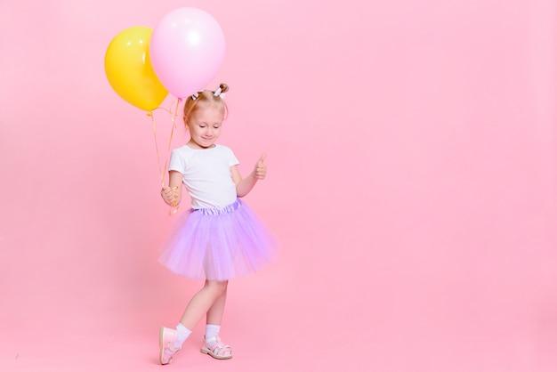 Grappig babymeisje in wit t-shirt en lila rok met ballonnen op roze achtergrond. kinderportret met ruimte voor tekst.