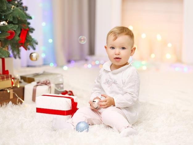Grappig babymeisje met kerstspeelgoed in de buurt van de kerstboom