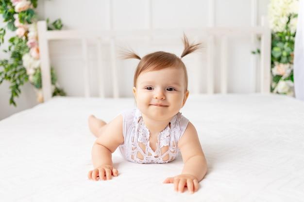 Grappig babymeisje van zes maanden oud ligt in een lichte, mooie kamer op een wit bed in een kanten romper en glimlacht