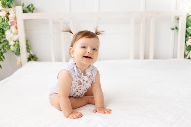 Grappig babymeisje zes maanden oud zittend in een heldere, mooie kamer op een wit bed