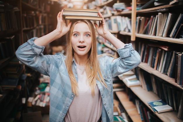 Grappig beeld dat van meisje zich dichtbij boekenrek bevindt. ze houdt twee boeken op haar hoofd met haar handen en kijkt recht vooruit. ze kijkt verbaasd.