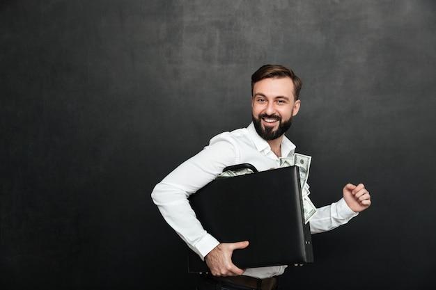 Grappig beeld van de gelukkige mens die zwart aktentashoogtepunt binnen van dollarbankbiljetten houdt, dat over donkergrijs wordt geïsoleerd