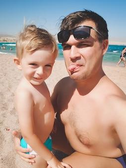Grappig beeld van een jonge man met zijn zoontje die tongen in de camera laat zien terwijl hij een selfie-foto maakt op het zeestrand. familie ontspannen en plezier hebben tijdens de zomervakantie vakantie.