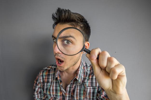 Grappig beeld van een knappe man spelen met een vergrootglas