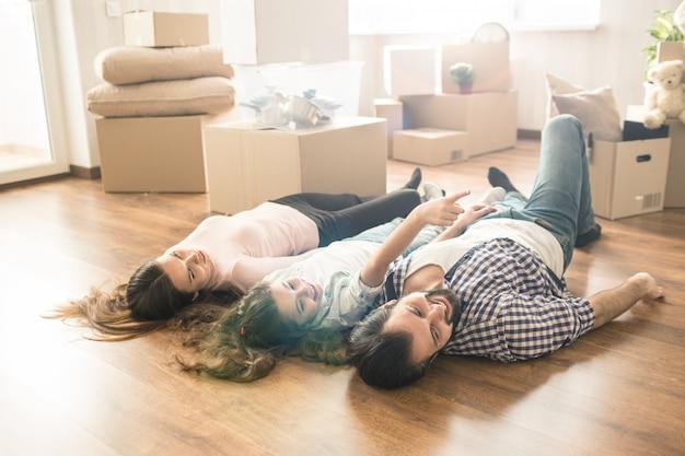 Grappig beeld van familie liggend op de vloer in hun eigen nieuwe appartement. ze hebben veel plezier samen. ook kijken ze ergens naar rechts.