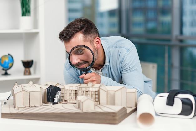 Grappig beeld van mannelijke architect kijkt door vergrootglas naar een huismodel. huisinspectie en onroerend goed concept.