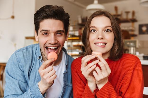 Grappig beeld van mooie gelukkige paarman en vrouw, en het eten van macaronkoekjes