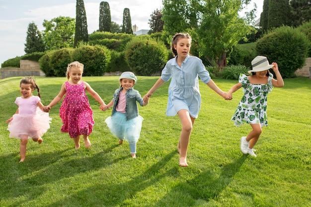 Grappig begint. kindermode concept. de groep tienerjongens en meisjes die bij park rennen. kleurrijke kinderkleding, lifestyle, trendy kleurenconcepten.