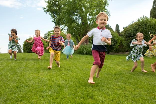 Grappig begint. kindermode concept. de groep tienerjongens en meisjes die bij park rennen.