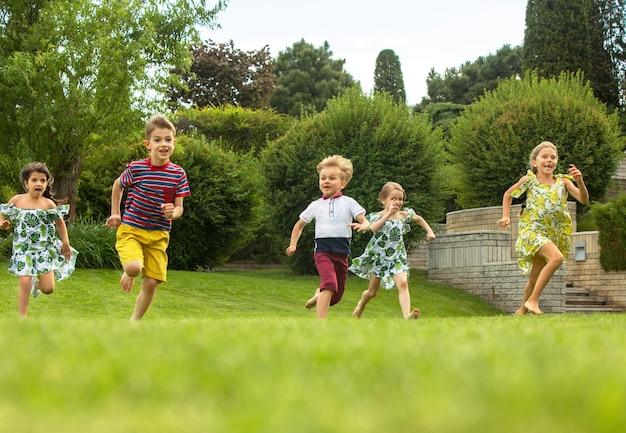 Grappig begint. kindermode concept. groep tienerjongens en meisjes die bij park lopen. kleurrijke kinderkleding, lifestyle, trendy kleurenconcepten.