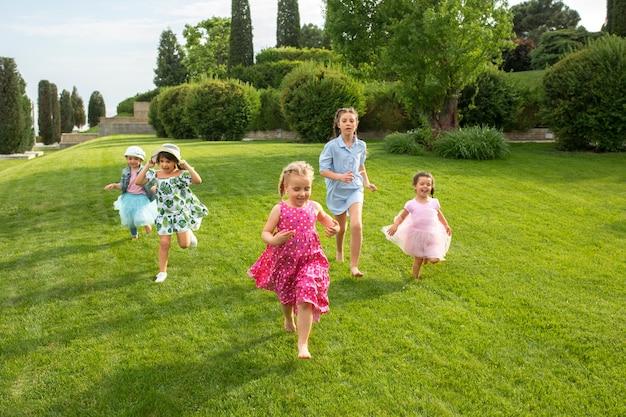 Grappig begint. kindermode concept. groep tienerjongens en meisjes die bij park lopen