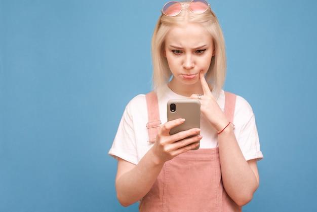 Grappig blond meisje in schattige kleding met een doordacht gezicht maakt gebruik van een smartphone op een blauwe achtergrond, focus op de telefoon in de handen van het meisje