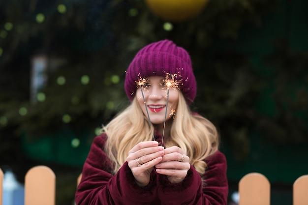 Grappig blond model met gloeiende bengaalse lichten bij de belangrijkste kerstboom in kiev. vervagingseffect