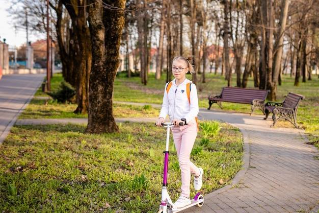 Grappig blondemeisje die op witte autoped in het warme groene park in het centrum van grote stad leren schaatsen. zomer activiteit