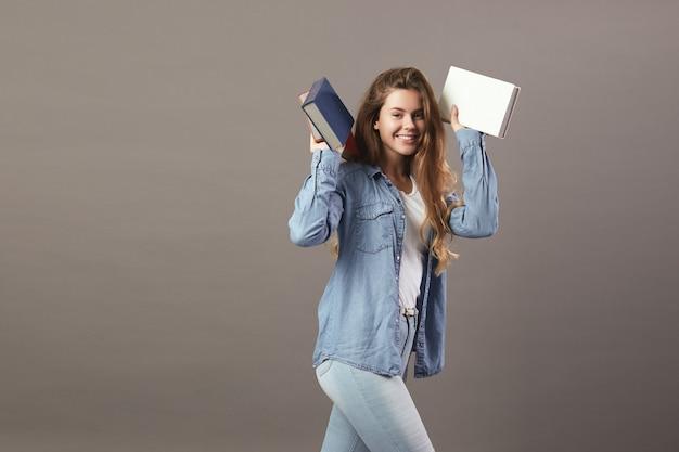 Grappig bruinharig meisje gekleed in een wit t-shirt, jeans en jeans houdt boeken in haar handen op een grijze achtergrond.